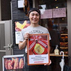 入賞メダルのパネルとともに喜びを語る、店主の宮崎義仁さん